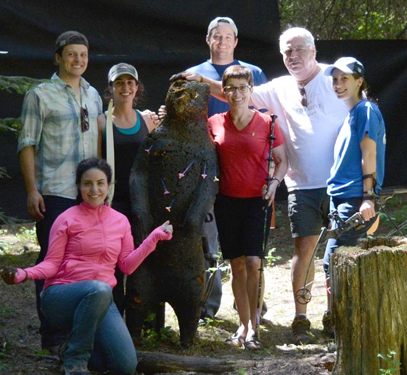 group posing with wooden bear
