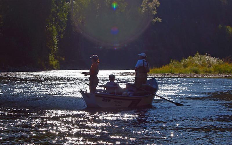 group fishing off a boat on the river