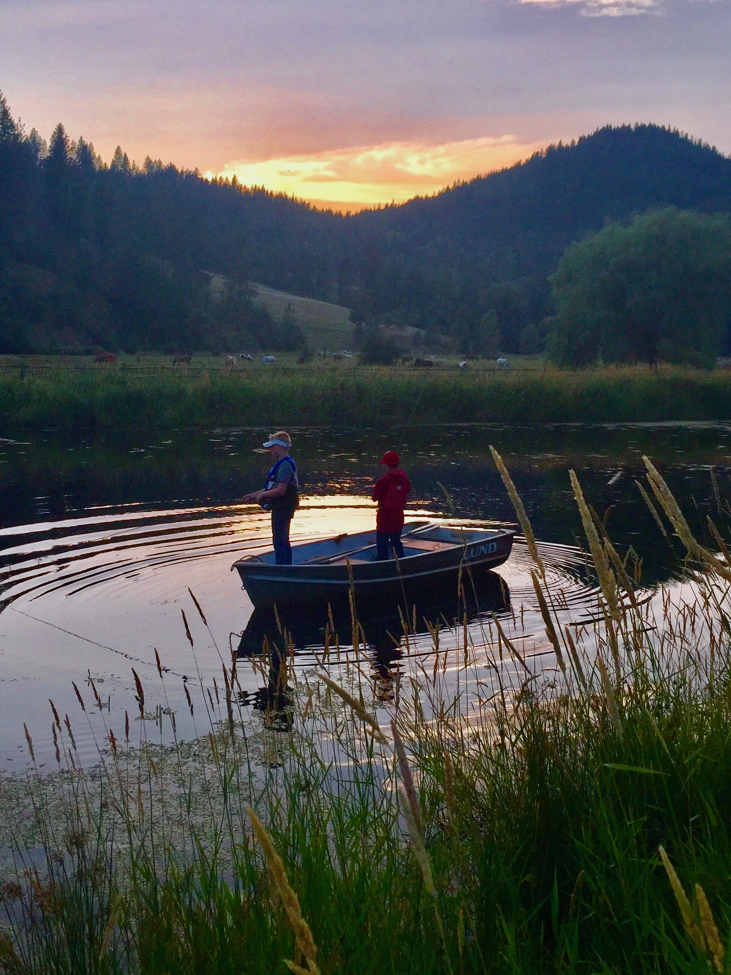 Two people pond fishing at sunrise.