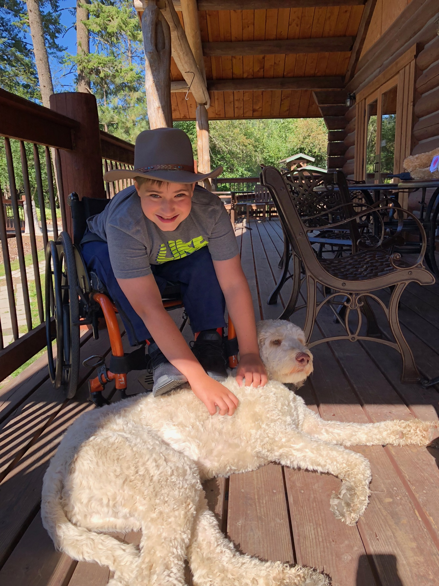 Young boy petting Willie the dog.