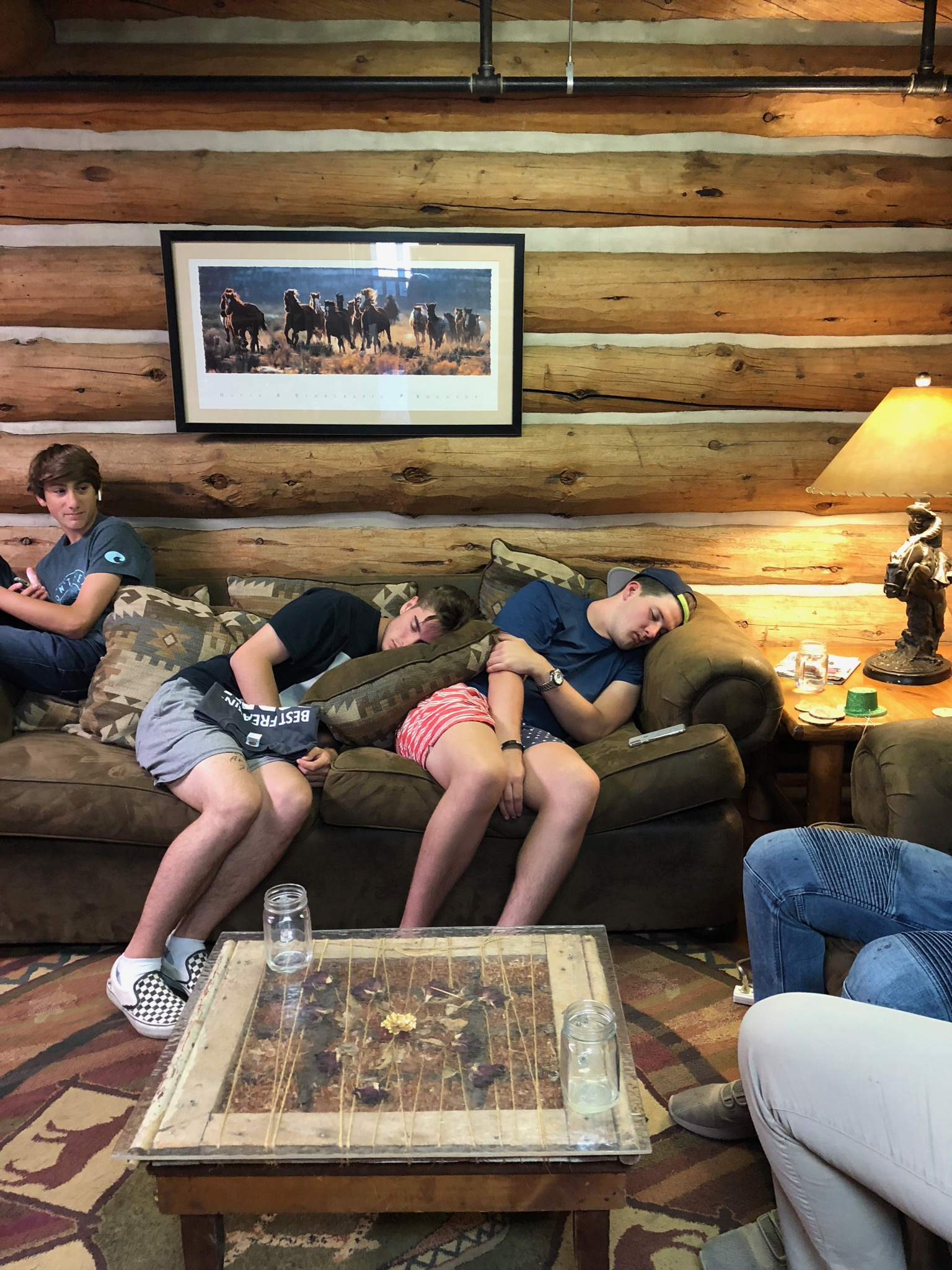 Young men napping on a sofa.