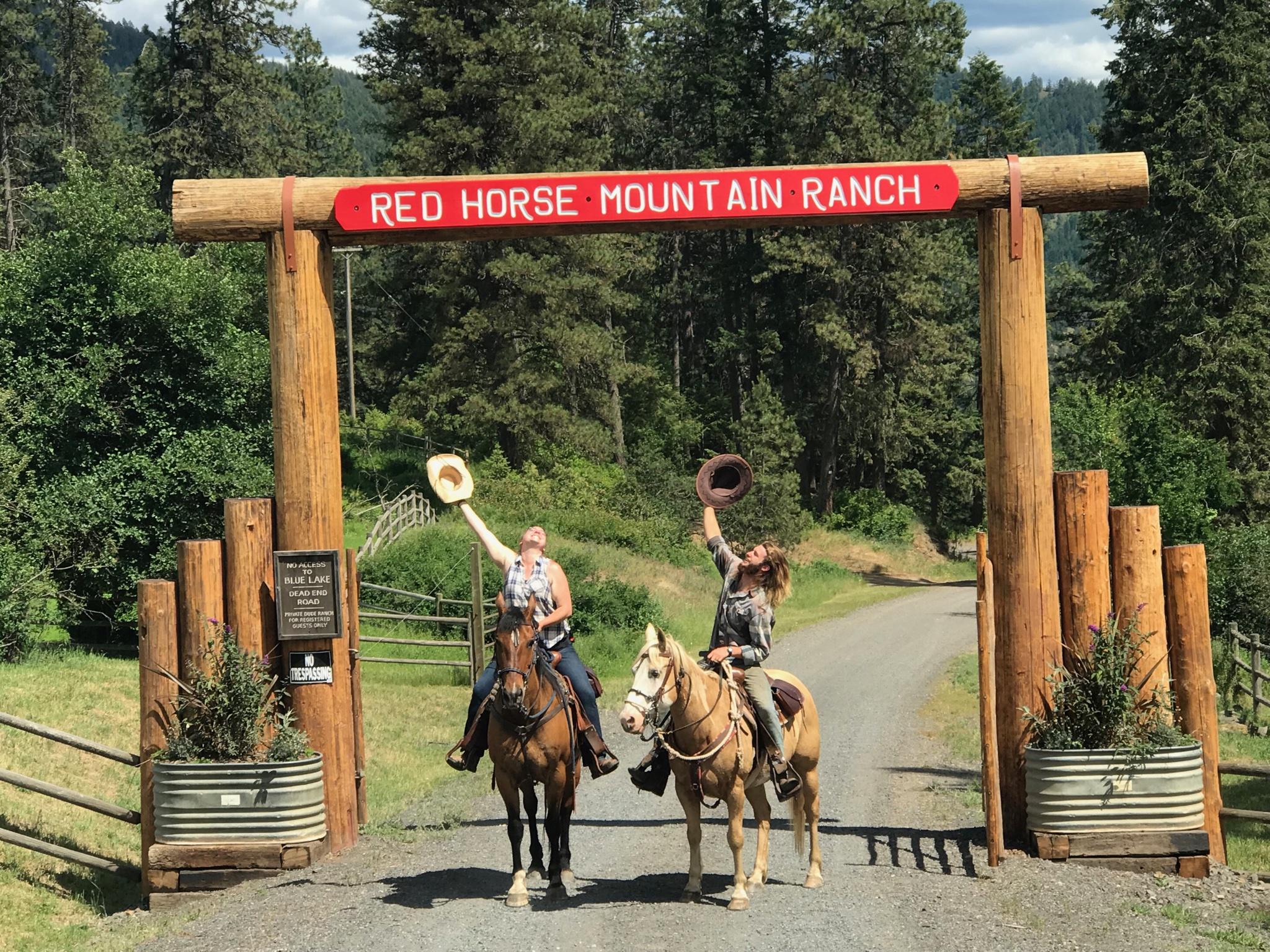 People on horseback under the ranch entrance sign.
