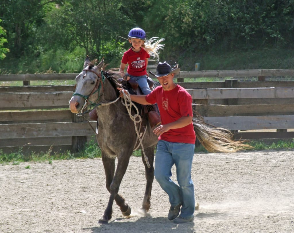 Wrangler helping a young woman with her horse.