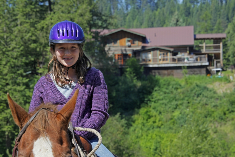 Young woman on horseback, lodge in the background.