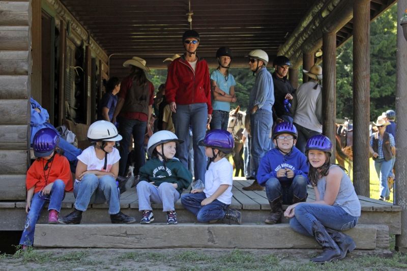 Young people on porch with riding helmets.