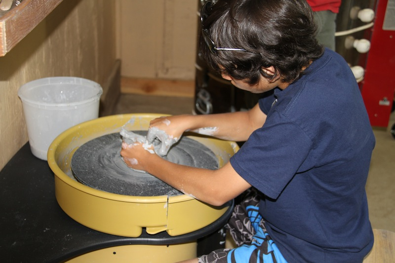 Young person making pottery.