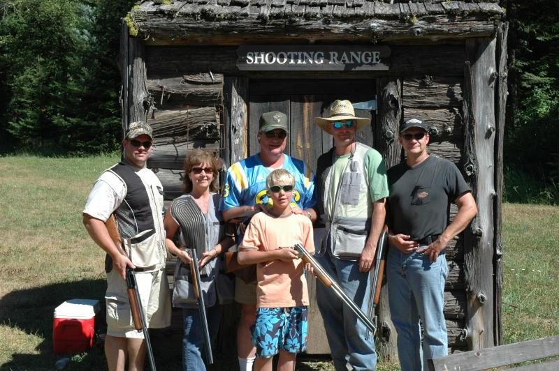 Family posing at shooting range with shotguns.