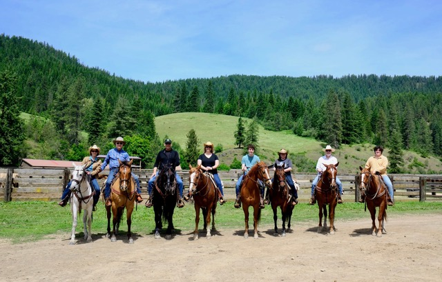 A family sits upon their steeds for a picture to commemorate their Idaho vacation.