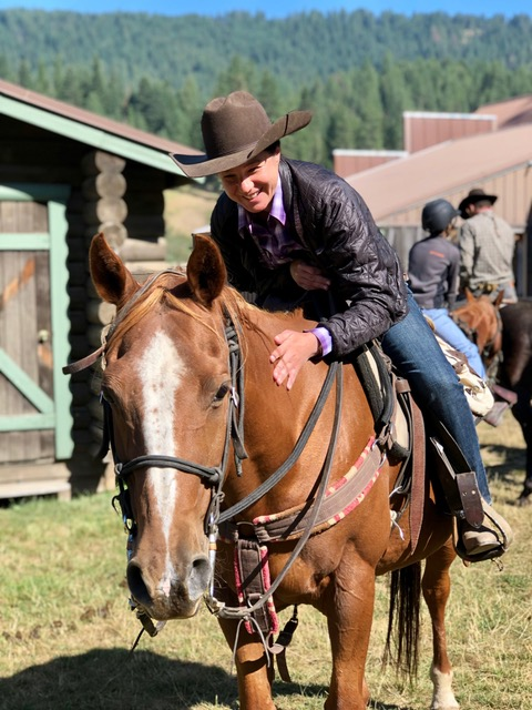 An avid horseback rider gleeful pats their trusty steed while enjoying a singles retreat.